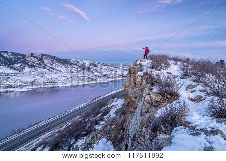 hiking Colorado before sunrise - male hiker on cliff above Horsetooth Reservoir in winter scenery