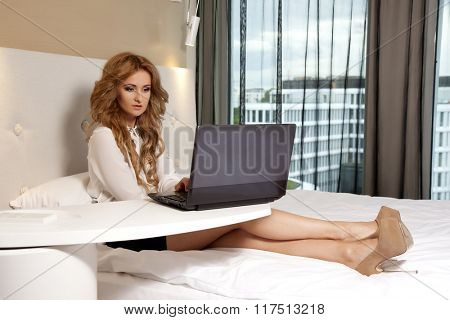 Portrait of a young adult beauty attractive sexy and sensuality happy pretty blonde businesswoman using laptop while lying on bed in hotel bedroom