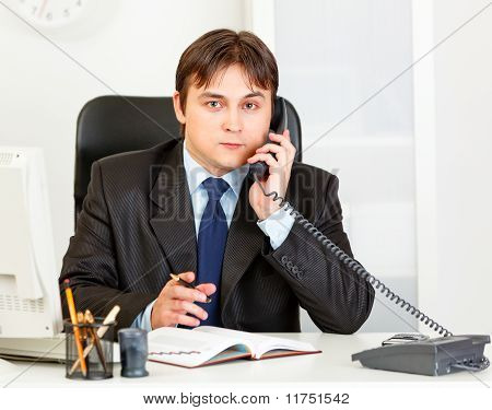 Thoughtful modern business man talking on phone and making notes in diary