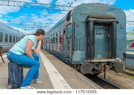 Woman Sitting On A Suitcase And Looking At The Departing Train