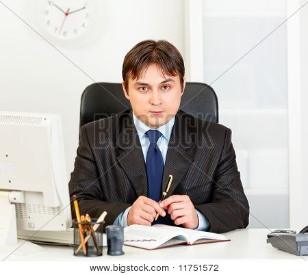 Serious modern business man looking at camera sitting in office