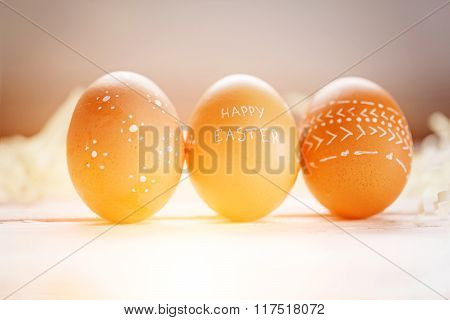 Three Brown Easter Eggs With Ornament And Text Happy Easter.