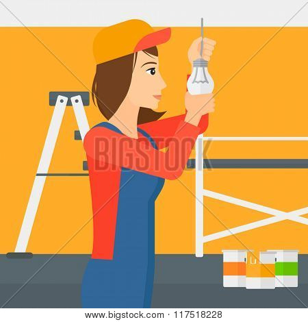Electrician twisting light bulb.