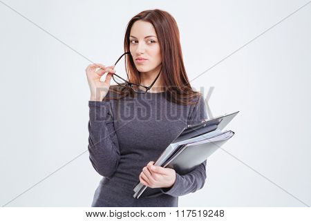 Young businesswoman holding folders and glasses isolated on a white background