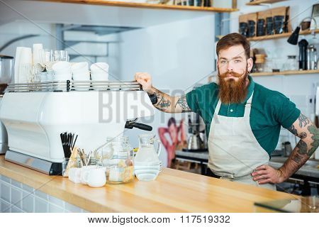 Portrait of handsome barista with beard and tattoo on hands standing near coffee machine in coffee shop