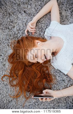 Happy redhead woman lying on the carpet and listening music on smartphone at home