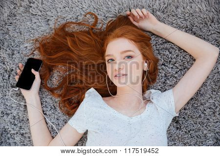 Redhead beautiful woman lying on the carpet and listening music on smartphone at home
