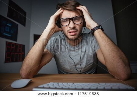 Frowning young man in earphones and glasses sitting with hands on head in front of computer