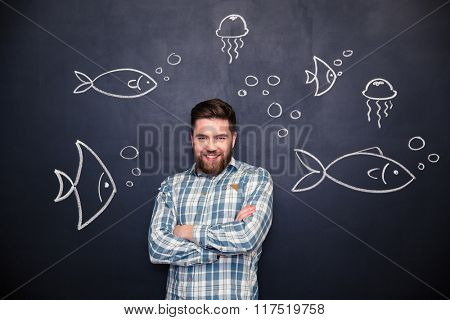 Cheerful handsome bearded young man standing with folded hands over blackboard background with drawn fishes and jellyfishes