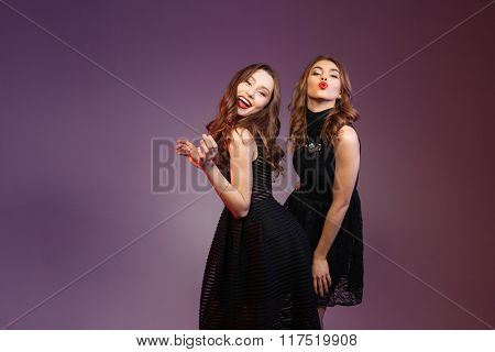 Two happy beautiful young women in black dresses dancing and sending kisses over colorful background