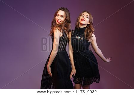 Two attractive young woman in black dresses dancing on party over purple background