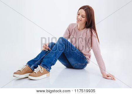 Smiling casual woman sitting on the floor isolated on a white background