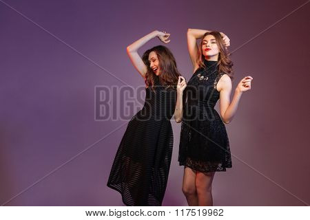 Two cheerful pretty young women dancing and smiling over colorful background