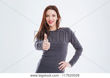 Smiling gorgeous young woman with red lips and long hair standing and showing thumbs up over white background