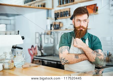 Handsome pensive man barista touching his beard and thinking in coffee shop
