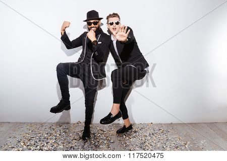 Two fashion man dancing on white background