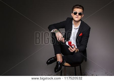 Young man in trendy cloth sitting on the chair and holding box with a proposal ring over black background
