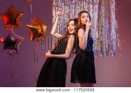 Happy two women in black dress drinking champagne over purple background
