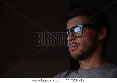 Portrait of handsome young man in glasses looking at screen