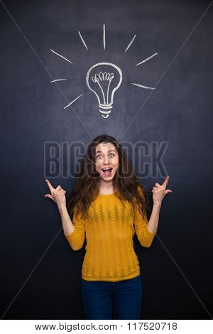 Happy surprised young woman ponting up with both hands over chalkboard background