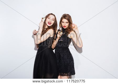 Two cheerful women posing in night dress with glass of champagne isolated on a white background