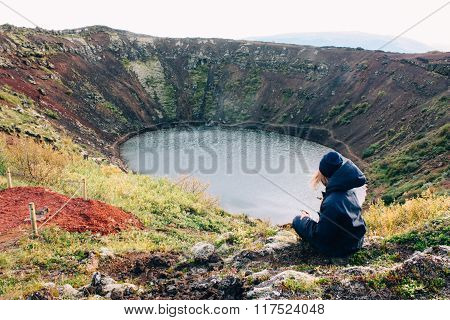 Lake hidden in eruption crater and girl, volcano landscape in Iceland
