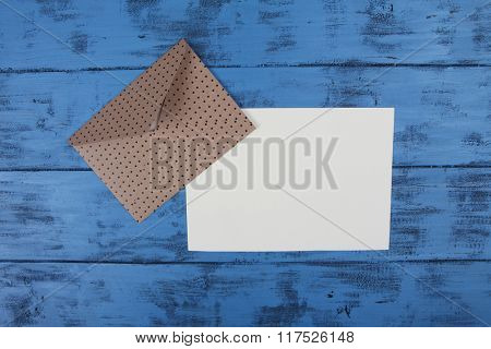 Brown envelope and blank paper sheet on blue wooden background