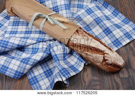 Homemade baked rye long loaf on blue towel