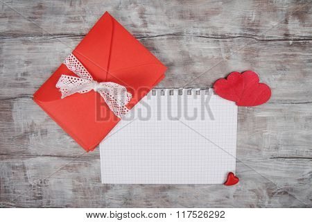 Valentine Day background with red envelope and wooden hearts