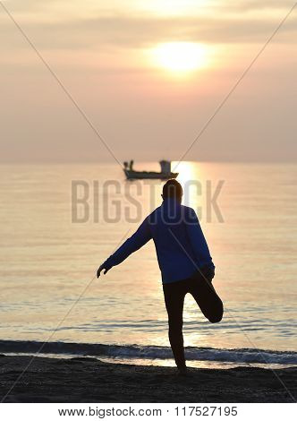 Silhouette  Young Sport Man Stretching Leg After Running Workout Outdoors On Beach At Sunset