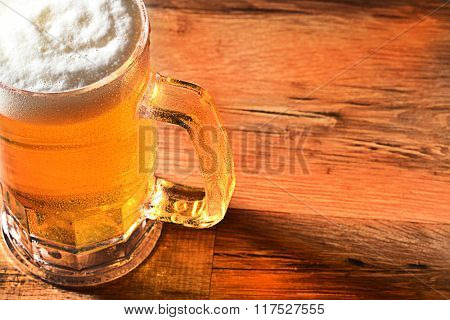 Closeup of a cold beer mug with a foamy head and copy space. High angle view with warm side light and reflections on wood table.