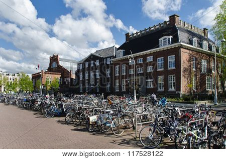 Many Bicycles Parked In Front Of The Traditional Buildings In Amsterdam Holland