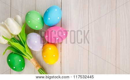 Easter eggs with bunch of tulip flowers on white wooden board