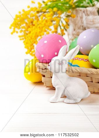Easter eggs with rabbit and branch mimosa. Isolated on white background