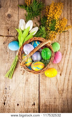 Easter eggs in wicker basket with copyspace and spring flowers on wooden board