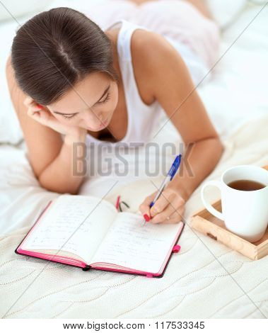 Young beautiful woman lying in bed writing a diary