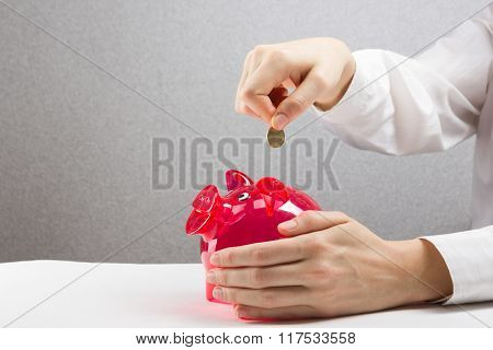 Savings Woman Putting Coin In Piggy Bank. Savings, finances, economy and home concept