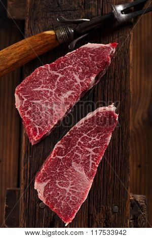 raw beef marbled steak with vintage utensils   on old wooden background