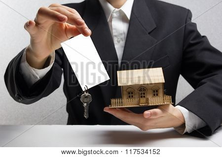Real estate concept. Hands holding blank business card with keys.