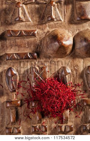 saffron spice in pile on carved wooden background