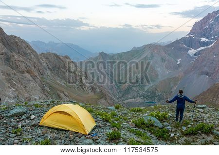 Hiker with walking poles and climbing tent