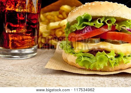 Cheeseburger,glass Of Cola And French Fries On Wooden