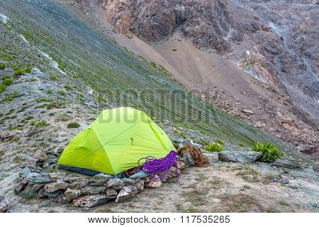 Green camping tent in mountains