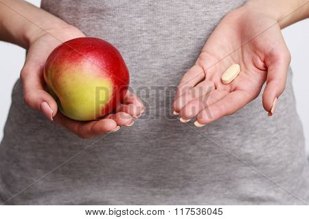 Close Up Woman's Hand Holding Pills, The Other Holding An Apple