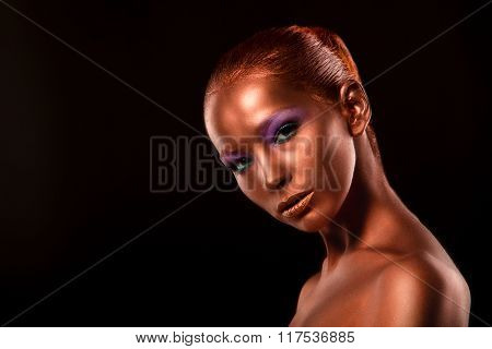 Gilt. Golden Woman's Face Closeup. Futuristic Gilded Make-up. Painted Skin bronze.
