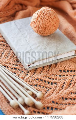 Old Notebook For Records, Ball Of Yarn And Knitting Needles Lying On Wooden Orange Knitted Plaid