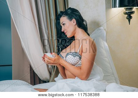 Portrait of beautiful young woman in nightwear holding coffee cup on bed.