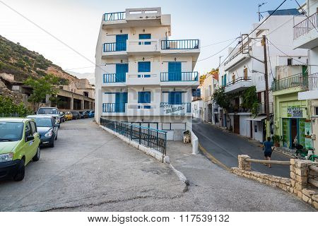 White living house with appartments and balconies in traditional Greek blue color