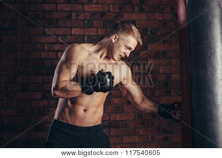 Boxer training on a punching bag in the gym.