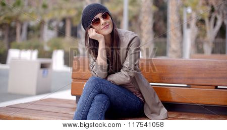 Happy relaxed trendy woman sitting daydreaming